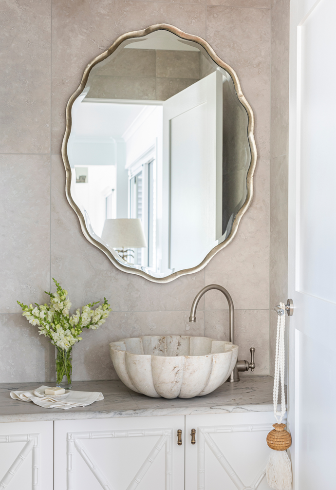 A stunning carved Italian marble basin rests atop a Macaubas granite vanity counter. The elegant, ornate mirror, sourced from Mirror Gallery, adds a sumptuous finishing touch.