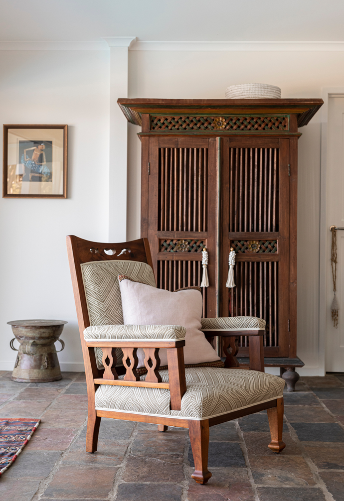 An antique Balinese dresser commands attention alongside another beautiful find – a vintage armchair.