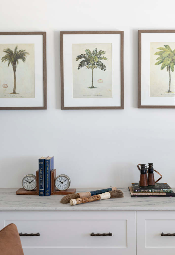 In the sitting corner of Jo and Steve's bedroom, a collection of framed prints found at One World Noosa hang above a Brazilian Macaubas granite-topped display unit. The eye-catching calligraphy brushes were purchased in Japan.