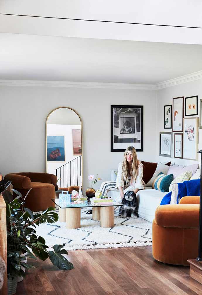 """Ana lounges on an MCM House sofa with Burger. The armchairs are by Sarah Ellison, the rug is Miss Amara and the mirror is from Life Interiors. The cushions are from [Matchesfashion](https://www.matchesfashion.com/au/