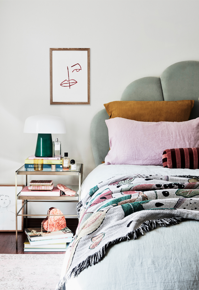 Ana's bedhead is By Designs, the table and lamp are West Elm, the bedding is from I Love Linen and Bed Threads and the throw is Slowdown Studio. On the bedside is a Maison Balzac glass and Respiro bag; on the floor is a Sylvia McEwan artwork.
