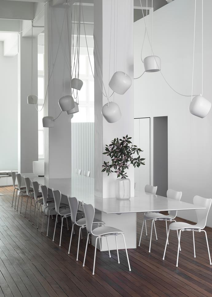 Fritz Hansen 'Series 7' chairs from Cult line the seven-metre marble table at the home's centre with a sculptural mass of Flos 'Aim' pendant lights dancing overhead, all finished in crisp white tones that highlight the original floorboards.