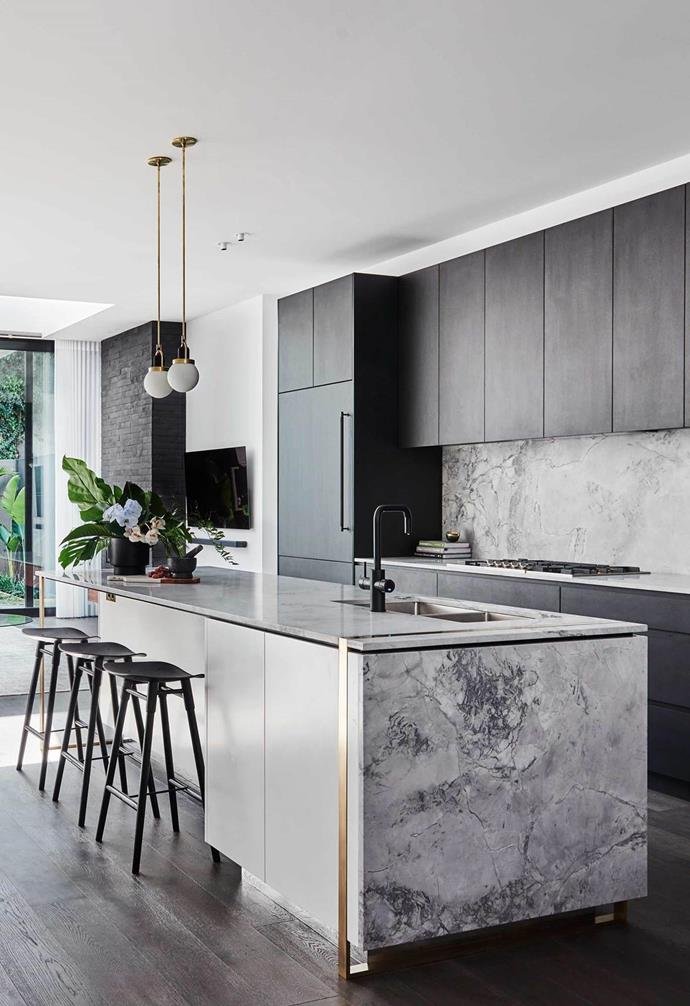 Charcoal kitchen cabinetry and grey, veined marble creates a decadent atmosphere.