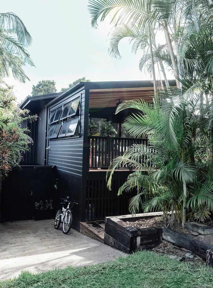 "Painting this [relaxed Byron Bay home](https://www.homestolove.com.au/beach-house-decorating-ideas-13529|target=""_blank"")'s exterior a dark colour accentuates its linear details and helps the house blend in with its tropical surrounds."
