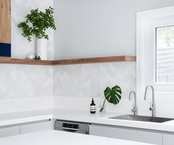 "Laid in a herringbone pattern, the splashback's 'Pixel' tiles from Urban Edge Ceramics nod to the 1930s and unite the other finishes, including the Alpine White Quantum Quartz benchtop and Laminex Oyster Grey cabinets. ""The tiles are textured with lots of different shades of white and grey,"" says designer Olivia. ""They visually pull together the various grey and white elements around the kitchen to create a cohesive look."""