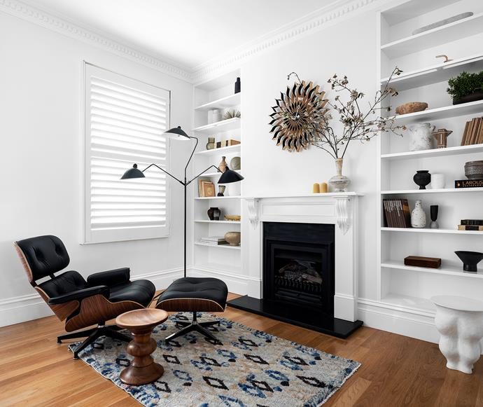Eames lounge chair, matching footstool, Eames turned-timber stool and Vitra 'Sunflower' wall clock, all Living Edge. Serge Mouille 'Lampadaire 3' floor lamp, Cult. Aerin 'Corvo' side table/stool, Palmer & Penn. Rug, Cadrys. Fireplace, Jetmaster.