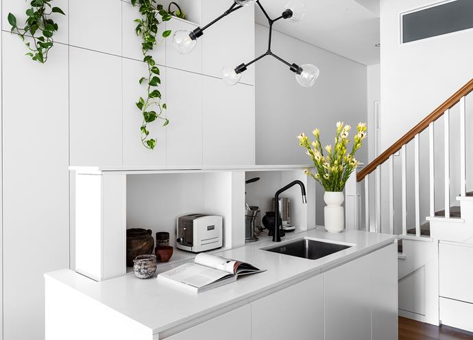 The compact but ultra-efficient kitchen includes a pop-up niche for small appliances within the island. It's powered by an A250 lift system by Nexus Construction Systems. Tapware, Abey.