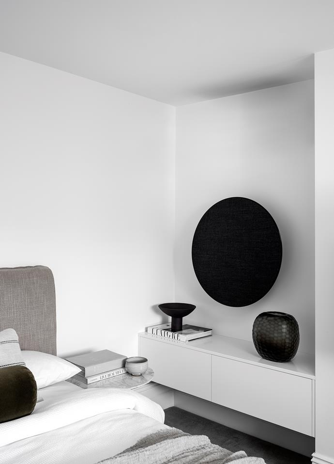 A Beoplay wall-mounted speaker from Bang & Olufsen hangs above a custom credenza by SED Joinery. Tulip side table by Eero Saarinen from Dedece. Vases from Conley & Co (left) and The DEA Store.