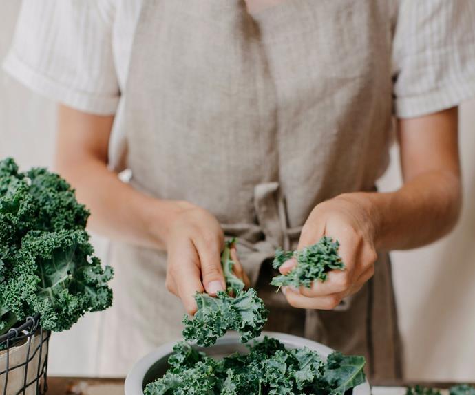 Person wearing apron making a kale salad