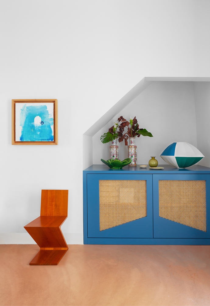 "The offbeat silhouettes of the sideboard, chair and objects work perfectly with the angular recessed wall. The blue sideboard is Letizia's own design, which a local artisan custom made. On top are Chinese vases from Letizia's family's private collection and an oval-shape lamp that she also designed and had made locally. The Zig-Zag chair is by Gerrit Rietveld and the [artwork on the wall](https://www.homestolove.com.au/how-to-hang-artwork-2203|target=""_blank"") is by the Italian artist Pizzi Cannella."