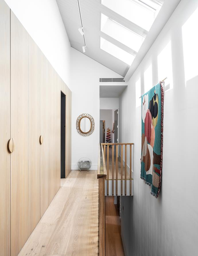 Oak-veneer wall cladding and balustrade designed by The Designer-Renovator. Timber cupboard handles, Auburn Woodturning. Skylights, Velux. Vintage Italian mirror, 506070. Wall art by Slowdown Studio, through Koskela.