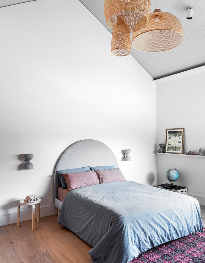 The V-groove ceiling and Double Cup wall lights by Anna Charlesworth are all painted Dulux Pozieres.Custom bed and bouclé-upholstered bedhead, The Designer-Renovator. Quilt cover, Adairs. Artek side table, Anibou. Pendants, Spence & Lyda. Artwork, Koskela.