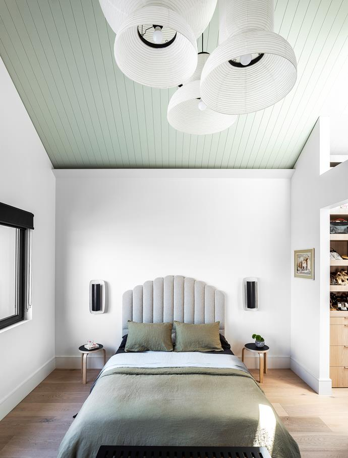 Shield wall lights by Anna Charlesworth reinforce the detail on the bed designed by Dean, The Designer-Renovator. Linen bedcover, Cultiver. Artek side tables, Anibou. Pendant lights, Great Dane. Vintage artwork. V-groove panelling on ceiling painted Dulux Pozieres.