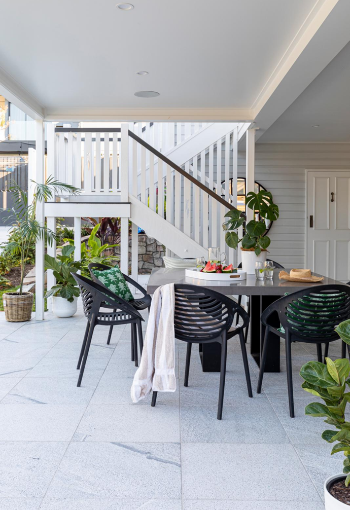A Pop Plus concrete table and Matt Blatt chairs create another casual outdoor dining area downstairs for pool guests.