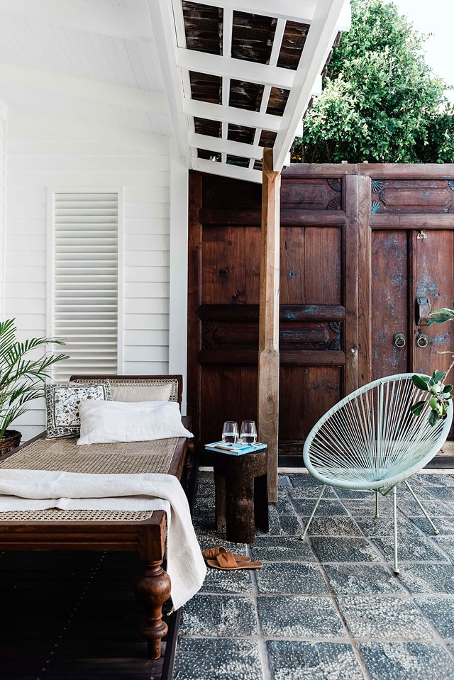 """Inspired by a love of south-east Asian style, a Queensland couple built a [home in Peregian Beach](https://www.homestolove.com.au/peregian-beach-house-22286 target=""""_blank"""") that makes everyday feel like a holiday. """"I love the little shell shape on the wall,"""" says owner Vicki of the salvaged wooden walls that frame the outdoor relaxation space."""