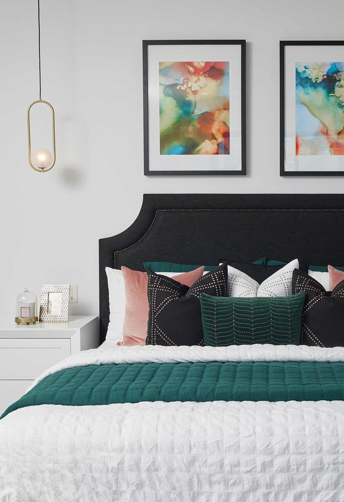 The master bedroom features a statement velvet bedhead and beautiful bedside lights that add a luxurious element to the room.