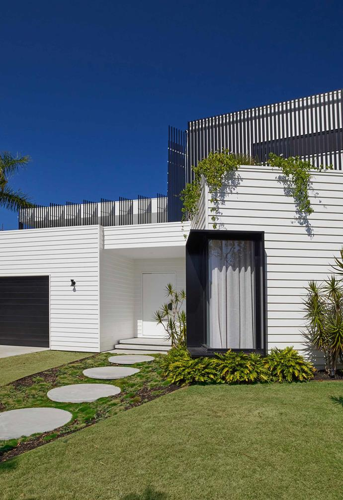 A beautifully manicured front lawn featuring statement circular pavers complements the white weatherboard facade of the house.