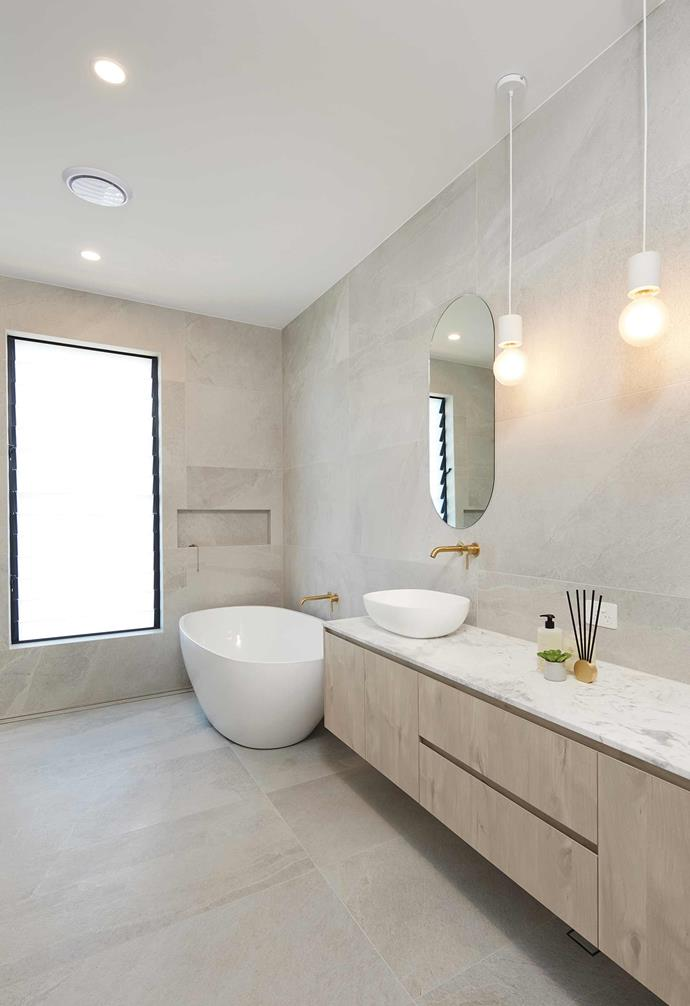 One of three bathrooms in the house, this space features a freestanding bathtub and a relaxed neutral palette.