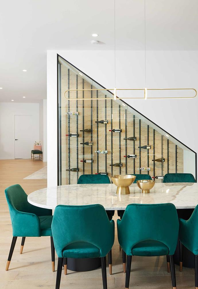The dining area features a marble-topped dining table and a suite of lush green velvet chairs. Tucked behind the dining zone is a wine storage space that adds a beautiful visual feature to the room.