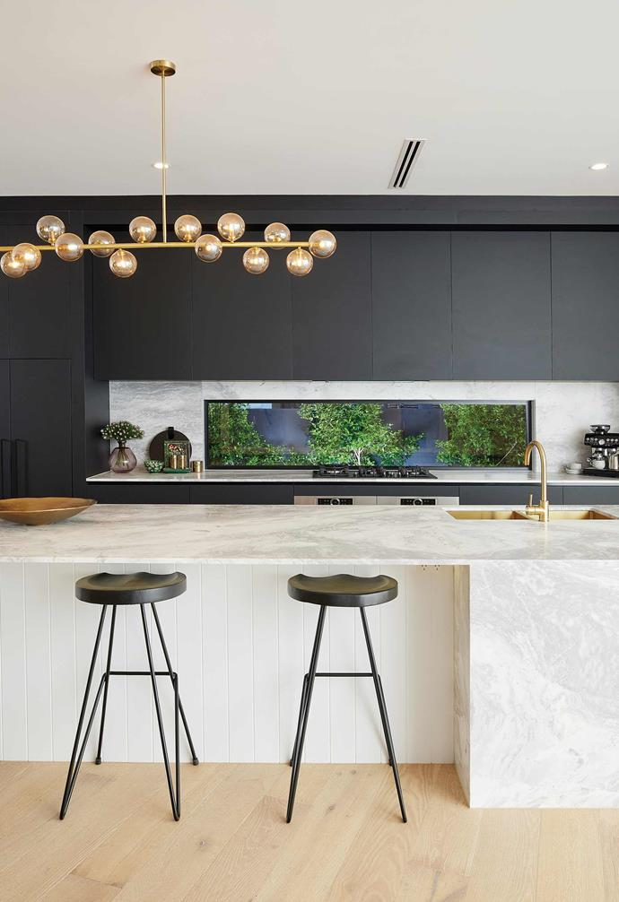 The kitchen features a statement marble benchtop paired with dark cabinetry, a striking pendant light, and brushed gold tapware.