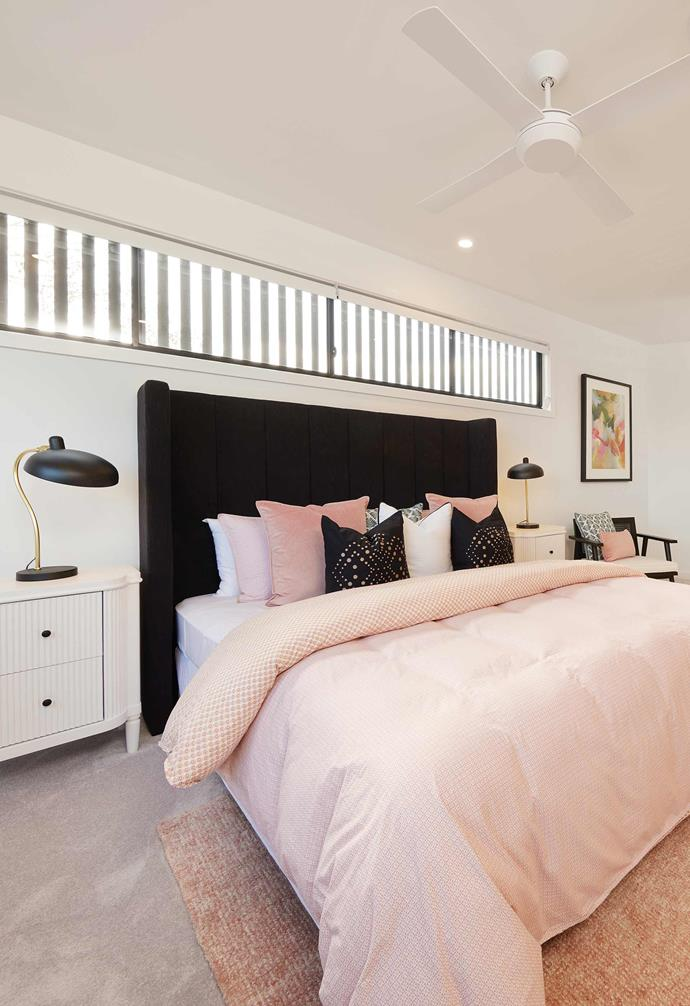 Pink bedding and a striking black velvet bedhead make a bold statement in this bedroom.