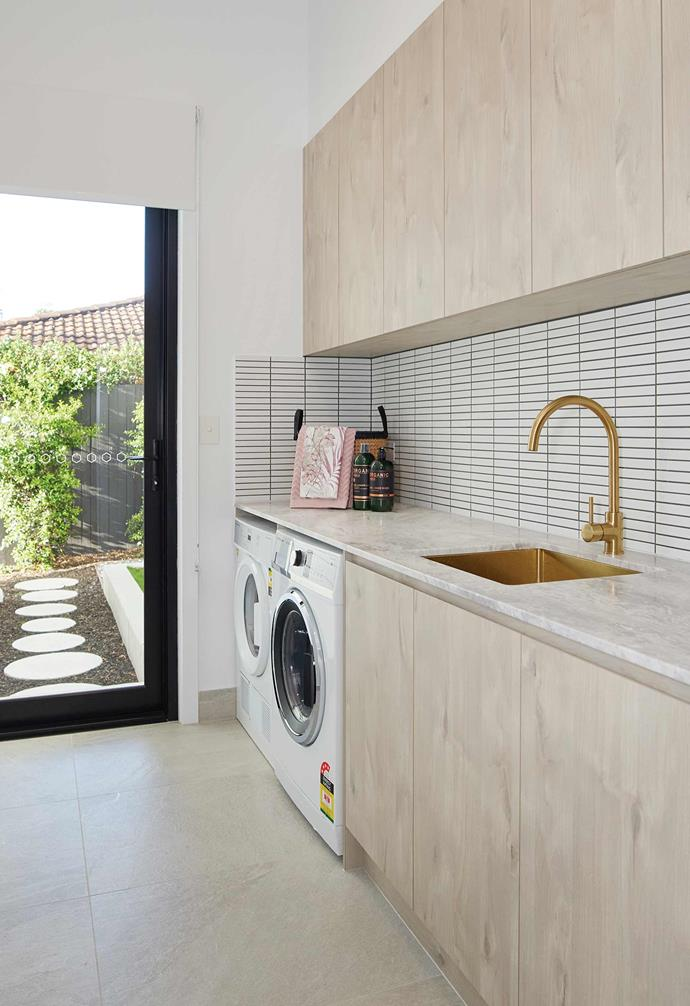 The laundry leads directly outdoors and features a kit-kat tile splashback as well as brushed gold tapware and sink that add a glamourous touch. Ample cabinetry adds a generous amount of storage above and below.