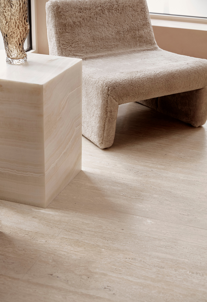 The Reeno occasional chair, covered in Australian sheepskin, is by Grazia & Co. It's paired with a sleek travertine plinth that functions as an accessories display.