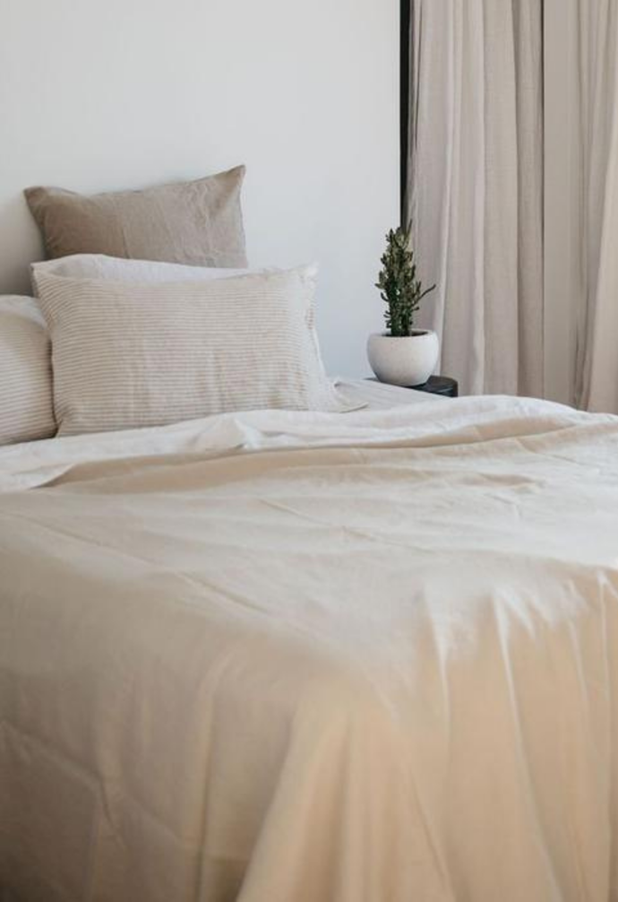 Neutral tones and layers create a peaceful aesthetic in a bedroom.