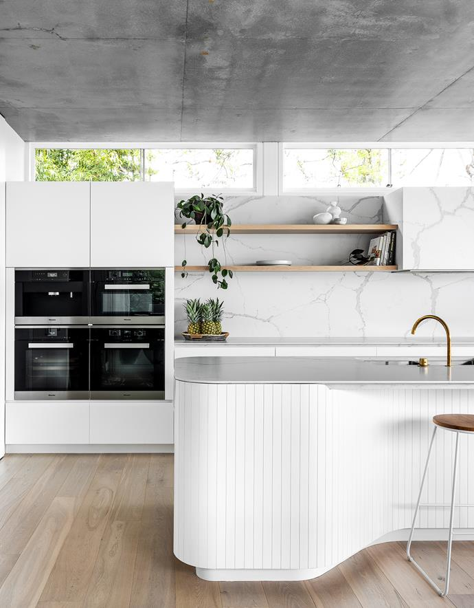 The sinuous island bench features custom-routed cladding. Talostone benchtops and splashback in Calacatta Luxe Matt. Tapware, Sydney Tap & Bathroomware. Open shelving in whitewashed American oak. Ovens, Miele. living Whitewashed American oak joinery, Braeside Joinery.