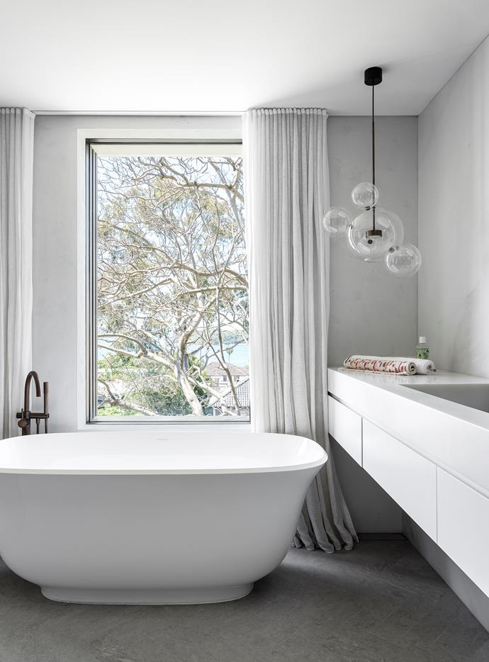 Victoria+Albert 'Amiata' bath, Reece. Brodware tapware, Candana. Bolle pendant light, available from Mondo Luce. Carrara Bianco marble vanity and wall panelling, Euro Marble. Azul Spanish limestone floor tiles, Sareen Stone.