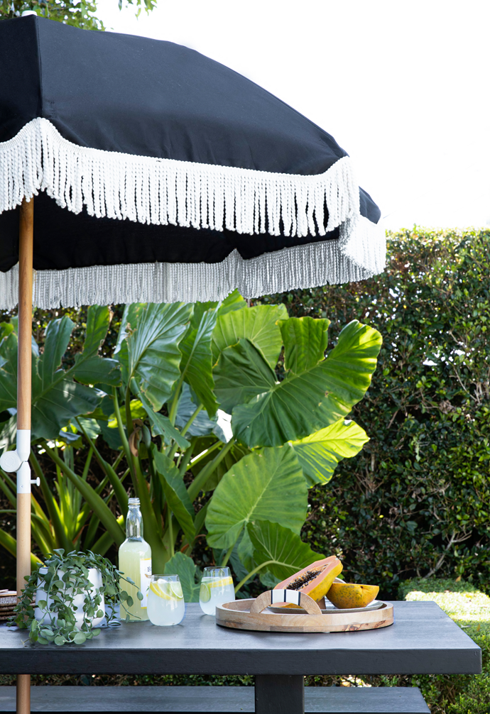 A Sunday Supply Co umbrella shades a Bunnings outdoor table.