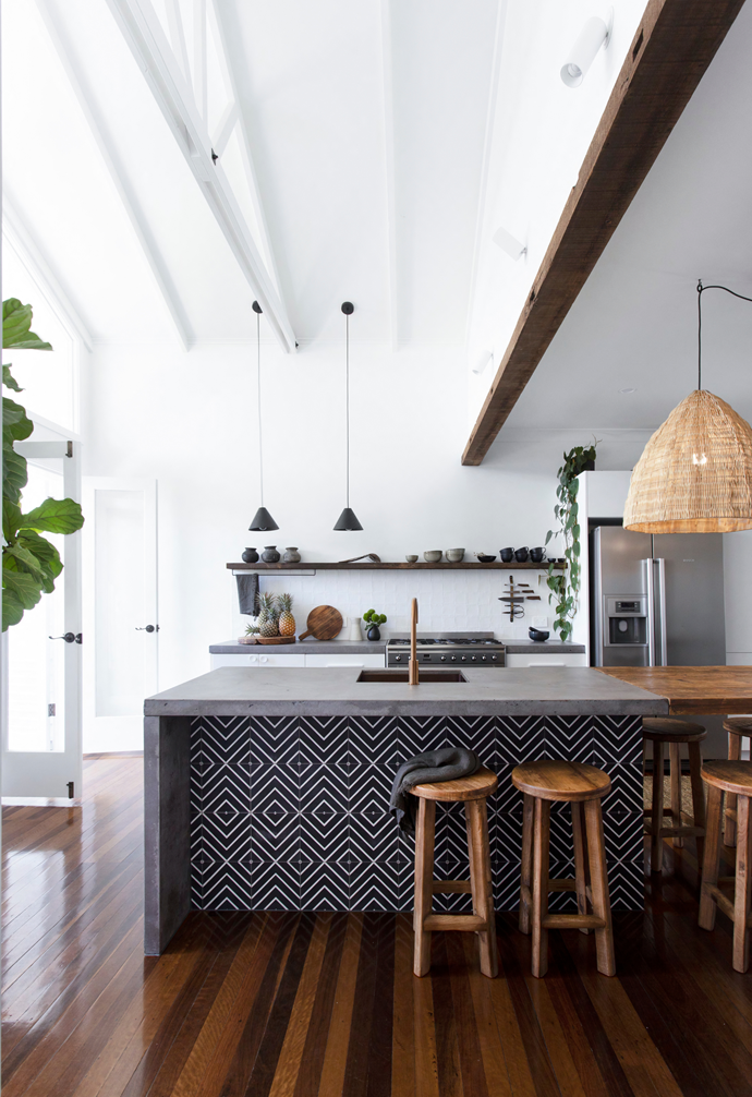 """""""The biggest risk we took was gutting our kitchen and renovating it ourselves,"""" Dave says of the space. Concrete benchtops were poured on site for an island that's a work bench at one end, with brushed copper sink and tapware, and casual dining at the other. """"I made it from a timber coffee table that was the perfect width,"""" Dave explains of the tactile surface, illuminated by pendants from CLO Studios. Along the back bench, cupboards were swapped for pendants from Beacon Lighting and a recycled timber shelf atop a splashback featuring textural Matt Avalon tiles from Tile Cloud"""