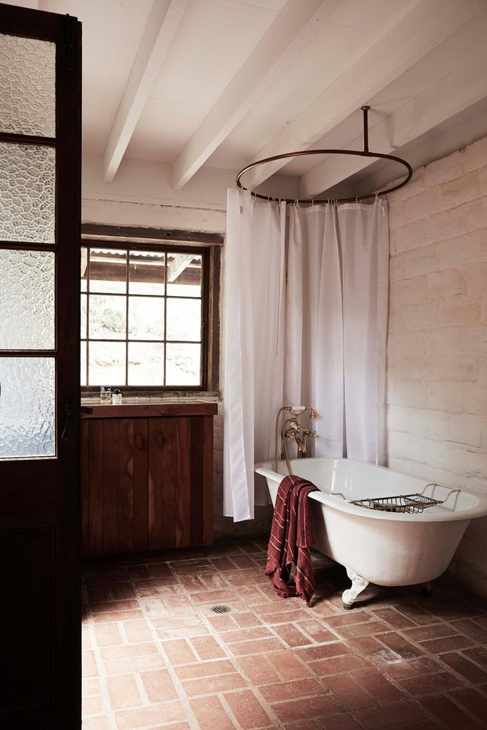 """Brick paved floors are carried throughout the home, including the bathroom, which features a classic [clawfoot tub](https://www.homestolove.com.au/freestanding-bath-design-ideas-4520