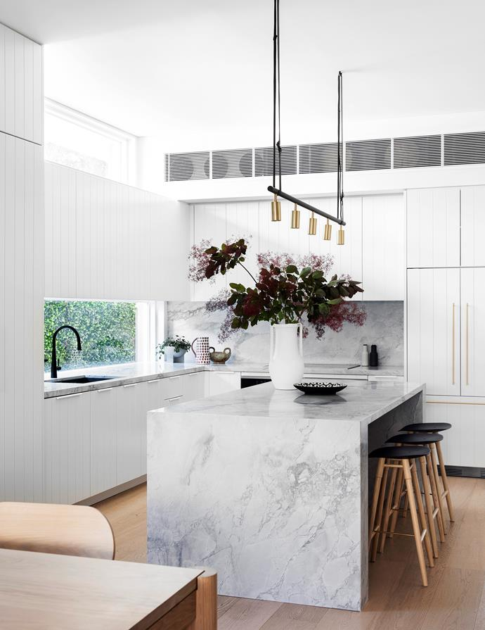 Clean lines and beautiful natural stone combine to create a deliciously light-filled and luxe kitchen conceived by Lara Ette Design. The cabinetry adds texture while the clean-lined benchtops ensure the room feels contemporary and fresh. Touches of brass create the effect of subtle jewellery in the room.