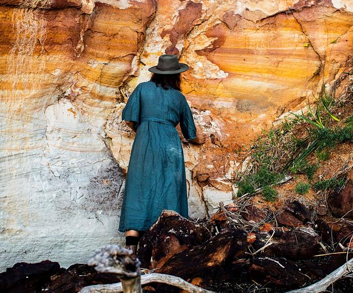 Woman wearing black dress and hat collecting ochre from rock in North Stradbroke Island
