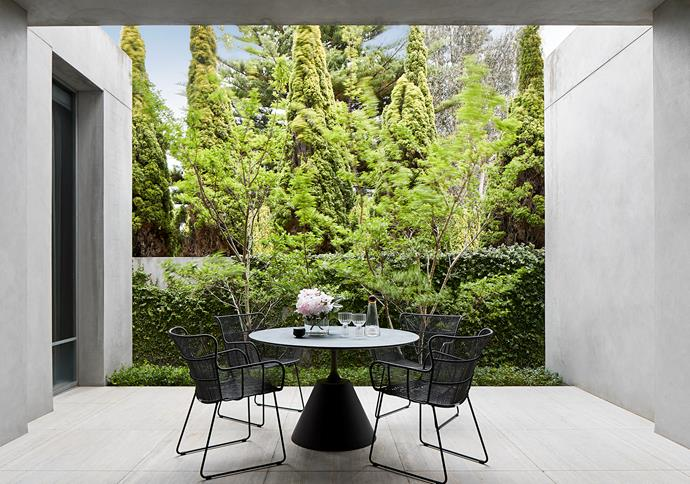 This intimate ground-floor courtyard runs alongside the formal living room and overlooks a stand of mature cypress trees. 'Amalfi' outdoor dining chairs from Coco Republic attend the 'Jenson' outdoor dining table from Horgans. Fferrone glasses from Hub.