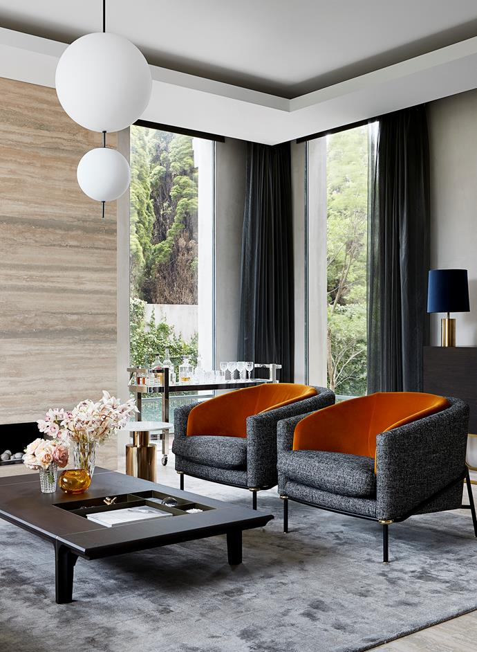In a corner of the formal living room on a rug from RC&D, Minotti 'Fil Noir' armchairs from De De Ce and 'Kendo' coffee table from Natuzzi with a When Objects Work vase from Hub. DePadova 'Elementi' pendant light from Boffi Studio. 'Rico' brass and marble side table from Horgans. The impressive fireplace is made from travertine which complements the silver travertine flooring.