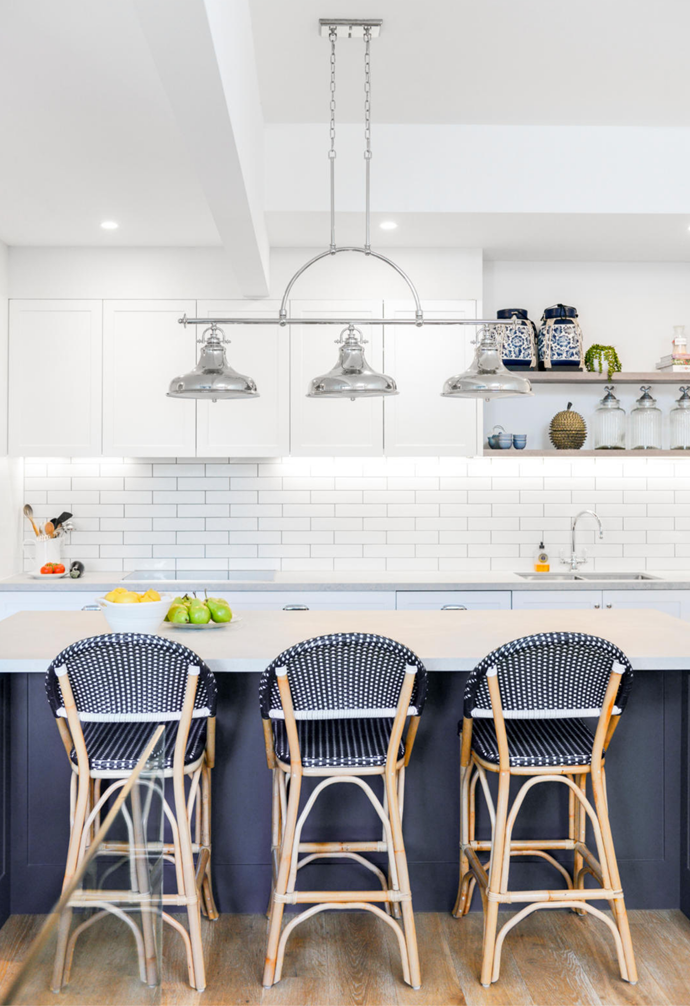 The matt finish of the Caesarstone island bench in Airy Concrete brings subtle star quality to this new kitchen, and is paired with 'Classique' bar stools in Navy and White from Lincoln Brooks. The benchtop is illuminated by an 'Emery' chandelier in Imperial Silver from Quoizel, which brings to life the elegant Hamptons style.