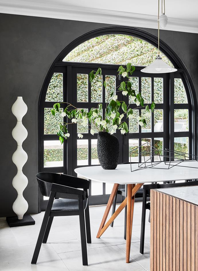 Arches are a recurring motif throughout the home, including in the kitchen, where a ceramic Connection totem sculpture by Katarina Wells from Curatorial+Co stands beside the Knoll 'Seito' dining table and Muuto 'Cover' armchairs, all from Living Edge. On the table, Tacchini 'Mantiqueira' vase from Stylecraft. Wire sculpture by Morgan Shimeld. 'Cobb Rise & Fall' pendant light from Dunlin.