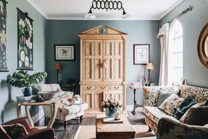 """We call this room the library - the English pine cupboard hides the TV,"" says Janes. She bought the floral Knole sofa in Gloucestershire, and had it upholstered in a crewelwork fabric found at the Salvation Army."