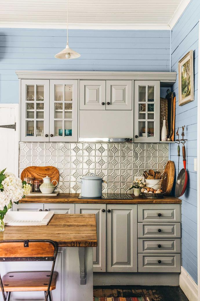 The kitchen features blue walls and a pressed tin splashback.