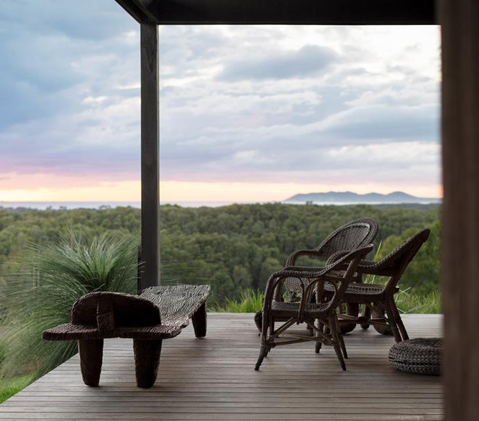 On a deck abutting the main living area, old seagrass chairs and a timber Senufo tribal bed, sourced years ago, lend a raw quality. Paperbark trees (*Melaleuca quinquenervia*) command the canopy of the Tyagarah Nature Reserve beyond.