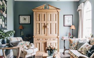 Blue country style living room with an antique French armoire in the centre
