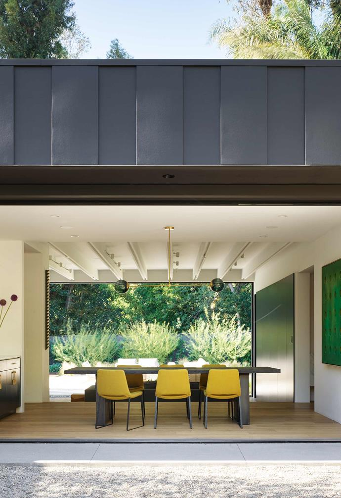 """**Dining area** This space faces the front courtyard. """"It's a balanced room of shapes and colour,"""" says interior designer Susan Mitnick. """"The table functions as a big architectural landmark."""" Custom dining table by Reeve Schley of [Seed LA Design + Build](https://seeddesignbuild.com/