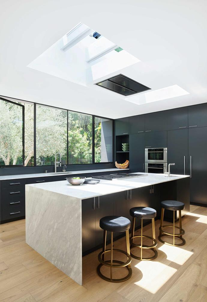 """**Kitchen** The importance of skylights in the flat-roofed design is most apparent here. Benchtops, Calacatta Crema. Cabinetry colour, Off-Black by [Farrow & Ball](https://www.farrow-ball.com/