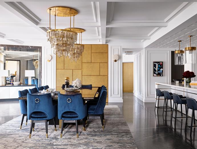 'Aegean' rug from Designer Rugs grounds a custom dining table with stone top and black-stained American Oak and satin brass base, and custom dining chairs with a stained frame and brass feet, all by Greg Natale. Behind the table, natural brass is wrapped over the wall panels. Visual Comfort 'Ardent' antique burnished chandeliers and 'Iveala' sconces, all by Kelly Wearstler. 'Halston' vase and 'Niemeyer' bowl on table by Greg Natale. Artwork by Antonia Mrljak from Becker Minty.