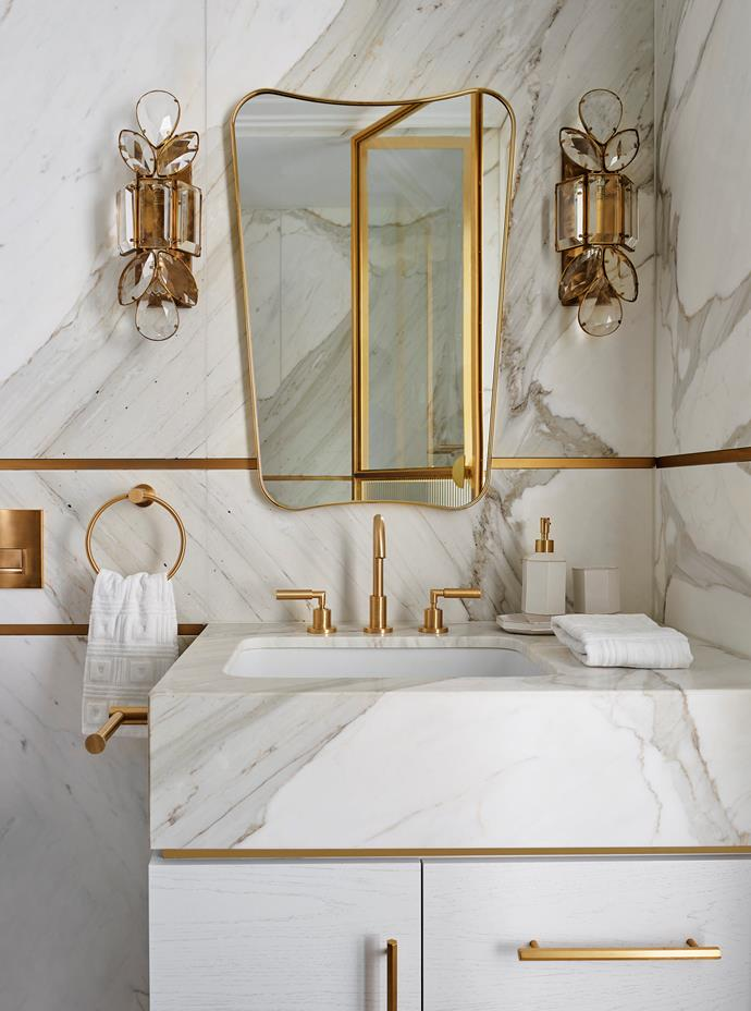 Brass is at its brilliant best in the upstairs bedroom ensuite, with a Gubi 'F.A.33' mirror from Cult flanked by Visual Comfort 'Lloyd' jewelled sconces. 'Icon' basin and 'Icon + Lever' basin set from Astra Walker. Cabinet pulls from Designer Doorware. Calacatta stone slab with brass trim inlay.