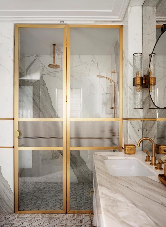 A mosaic of Thassos and Carrara marble with a brass inlay from Teranova was used for the floor of the ensuite. Calacatta stone vanity with brass trim inlay. 'Icon' basin and 'Icon + Lever' basin set from Astra Walker. Visual Comfort 'Liaison' sconce by Kelly Wearstler. 'Ava Gold' accessories from Labrazel.
