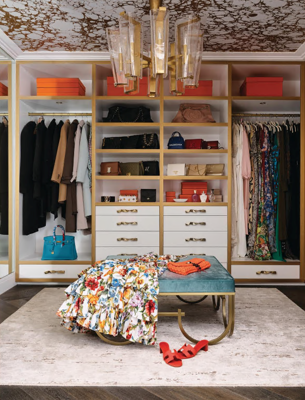 In the 'Hers' walk-in robe, the joinery unit features brass inlay and drawer pulls from Designer Doorware. Visual Comfort 'Alpine' chandelier by Aerin. Custom ottoman from Greg Natale. Vintage rug from Designer Rugs. 'Wabi' wallpaper in Cloud from Calico Wallpaper.