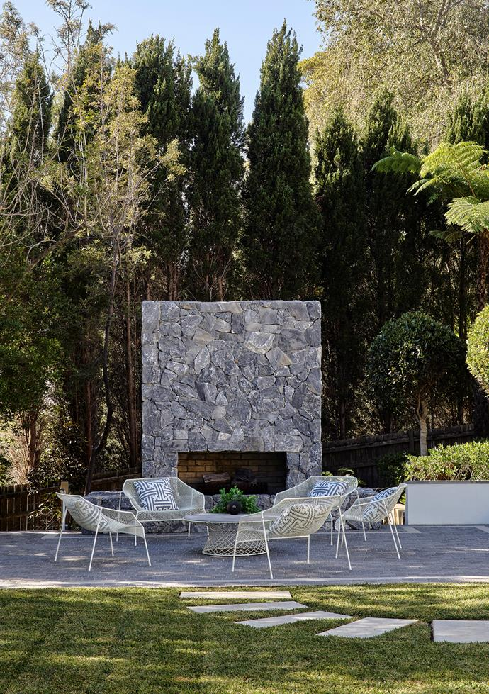 Afternoon shade adds to the serenity of the outdoor fireplace terrace. Emu 'Heaven' woven steel chairs and coffee table, all from Ke-Zu. Custom cushions in Gaston y Daniela fabric from Domestic Textile.